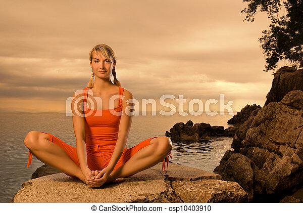 Beautiful young woman doing yoga exercise outdoors - csp10403910