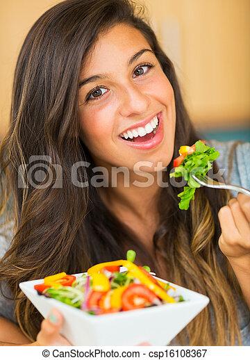 Beautiful young woman eating a bowl of healthy organic salad - csp16108367