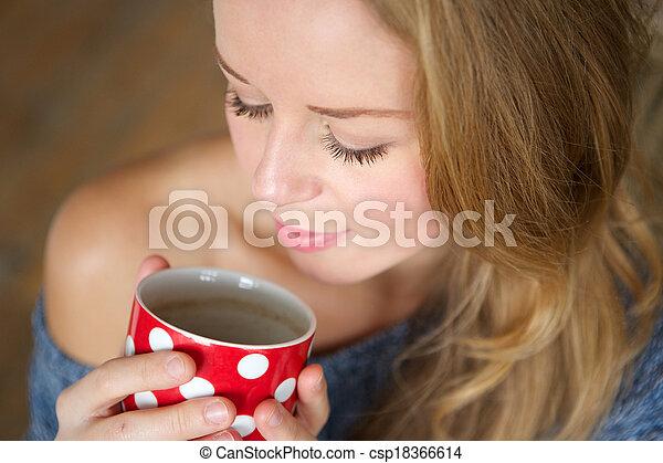 Beautiful young woman enjoying cup of tea at home - csp18366614