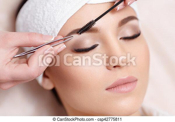 Beautiful young woman gets eyebrow correction procedure - csp42775811