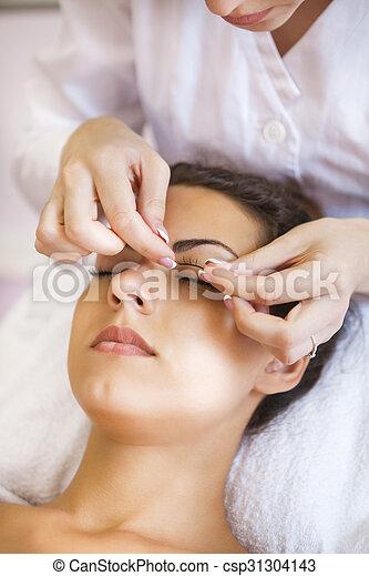 Beautiful young woman in cosmetic salon - csp31304143