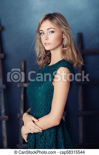 Beautiful young woman in green dress - csp58315544