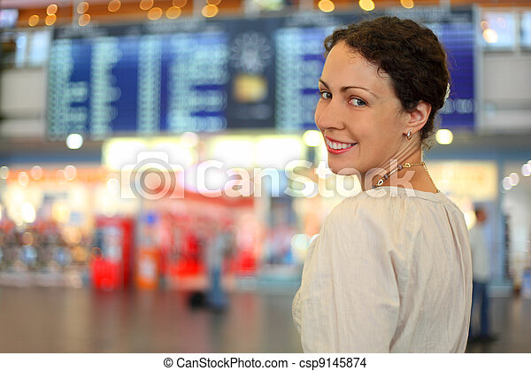 beautiful young woman in white wear in hall of airport, she smiles - csp9145874
