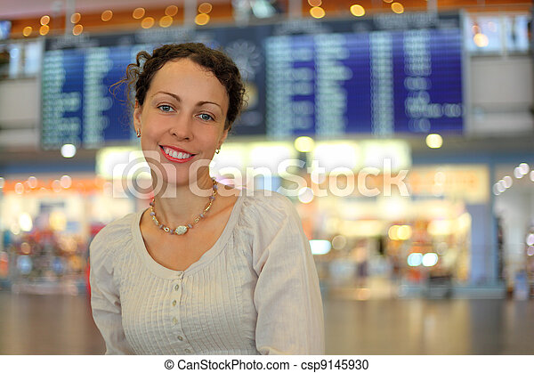 beautiful young woman in white wear in hall of airport, she smiles - csp9145930