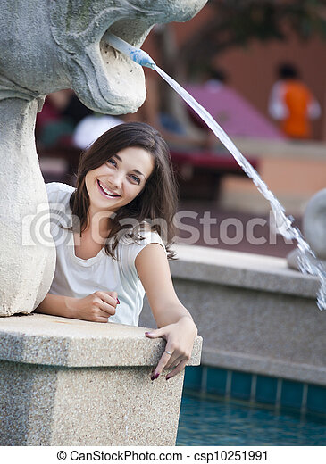 beautiful young woman is playing with fountain - csp10251991