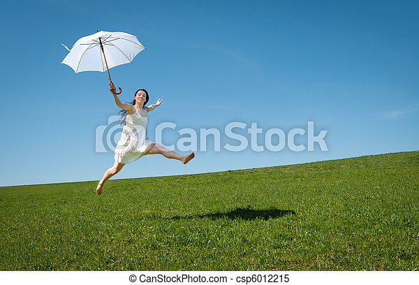 Beautiful young woman jumping with white umbrella - csp6012215