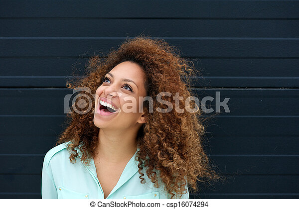 Beautiful young woman laughing outdoors and looking up - csp16074294