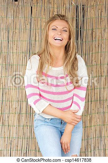 Beautiful young woman laughing outdoors - csp14617838