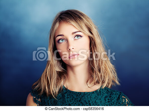 Beautiful young woman looking up on blue background - csp58356416