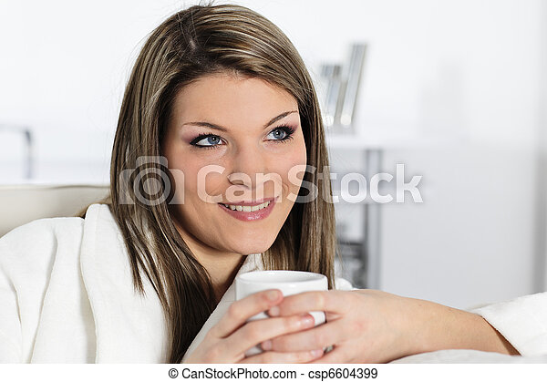 beautiful young woman on sofa with cup of coffee - csp6604399