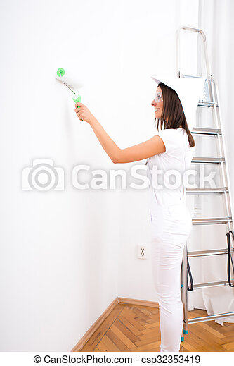 Beautiful young woman painting a Apartment - csp32353419