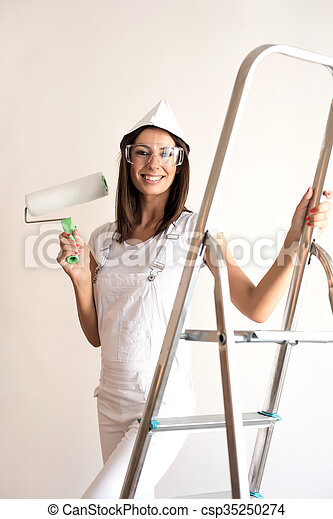Beautiful young woman painting a Apartment - csp35250274