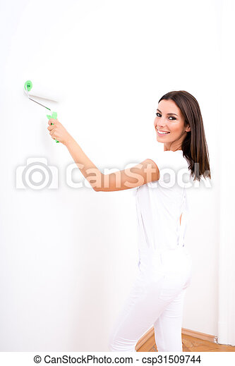 Beautiful young woman painting a Apartment - csp31509744