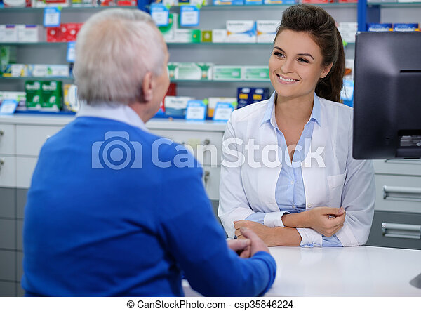 Beautiful young woman pharmacist talking with senior man customer in pharmacy. - csp35846224