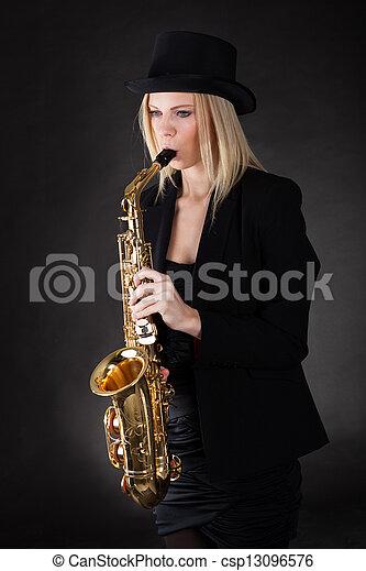 Beautiful young woman playing saxophone - csp13096576