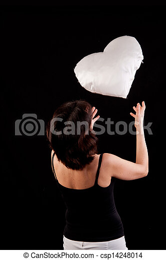 beautiful young woman playing with a white heart in hand - csp14248014