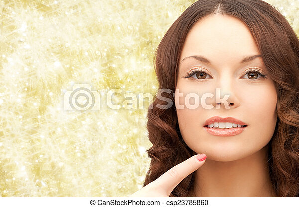 beautiful young woman pointing finger to her chin - csp23785860