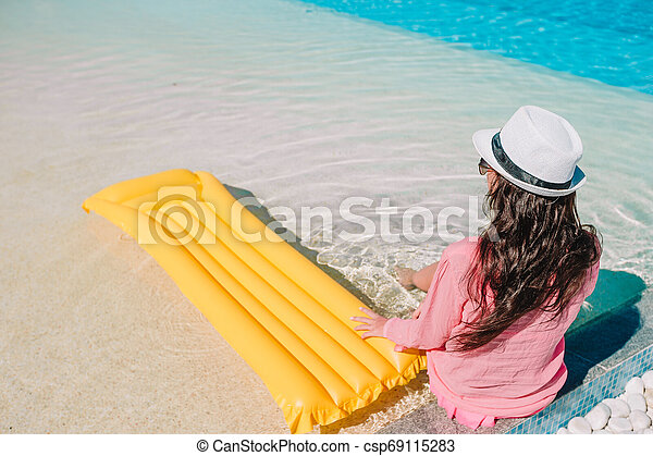 Beautiful young woman relaxing in swimming pool. Happy girl in outdoor pool at luxury hotel - csp69115283