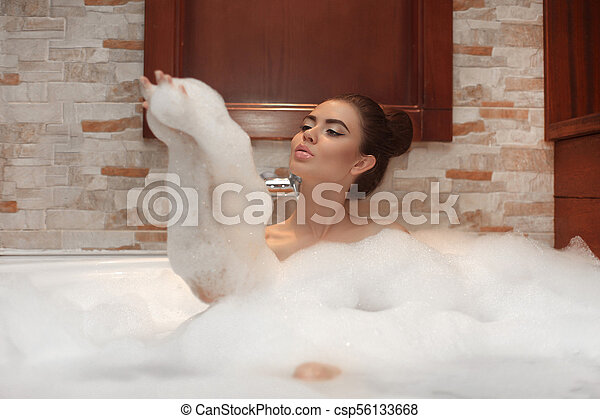 Beautiful Young woman relaxing in jacuzzi bath spa, Attractive girl with Clean Fresh Skin relaxing foam in bathroom. Beauty face skin care. Facial treatment brunette enjoying at home. - csp56133668
