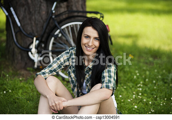 Beautiful young woman resting in park - csp13004591
