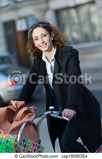 beautiful young woman riding bicycle in town - csp18580354