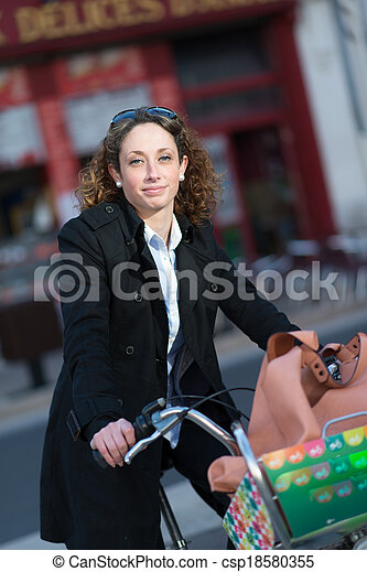 beautiful young woman riding bicycle in town - csp18580355