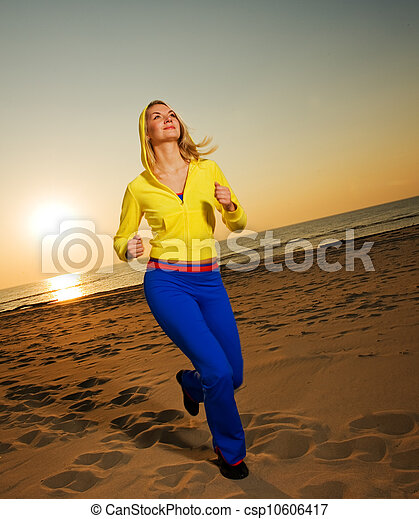 Beautiful young woman running on a beach at sunset - csp10606417