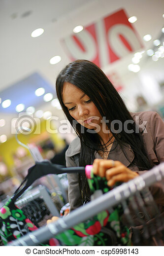 Beautiful young woman shopping in a store - csp5998143