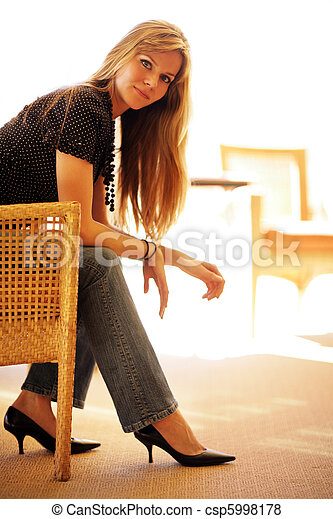 Beautiful young woman sitting in chair - csp5998178