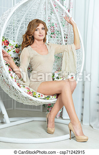 Beautiful young woman sitting in pendant chair - csp71242915