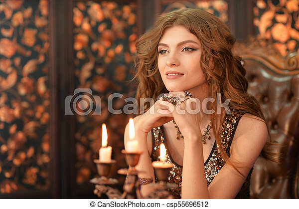 beautiful young woman sitting in vintage chair - csp55696512