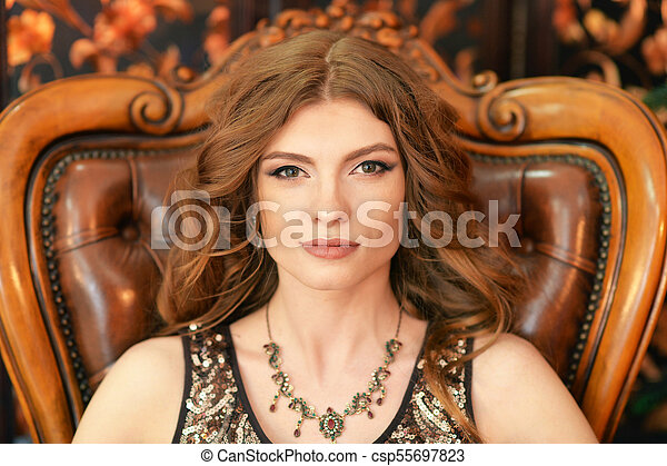 beautiful young woman sitting in vintage chair - csp55697823