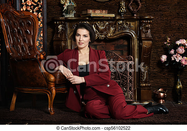 beautiful young woman sitting in vintage chair - csp56102522