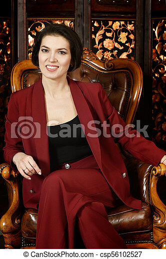 beautiful young woman sitting in vintage chair - csp56102527