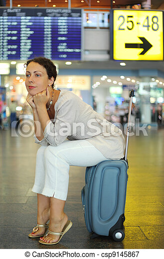 beautiful young woman sitting on their luggage in hall of airport and waiting airplane - csp9145867