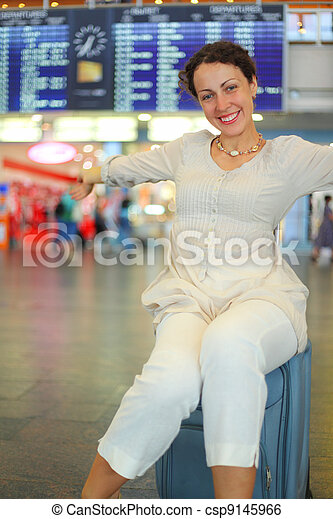 beautiful young woman sitting on their luggage in hall of airport - csp9145966