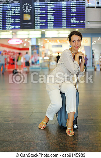 beautiful young woman sitting on their luggage in hall of airport - csp9145983