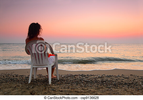beautiful young woman sitting on white plastic chair on beach and watching sunset, shallow depth of Focus - csp9136628