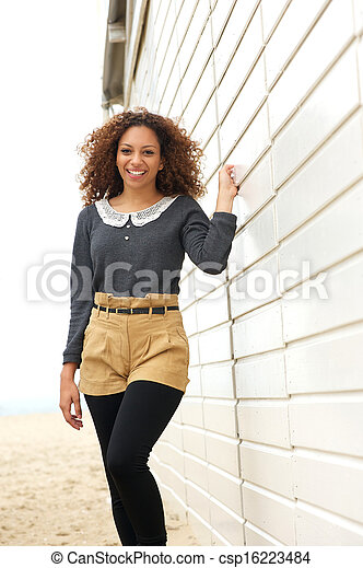 Beautiful young woman smiling and walking outdoors - csp16223484