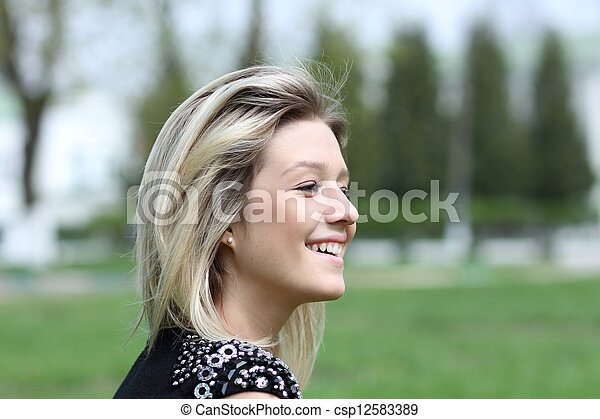 Beautiful young woman smiling. Outdoor portrait - csp12583389