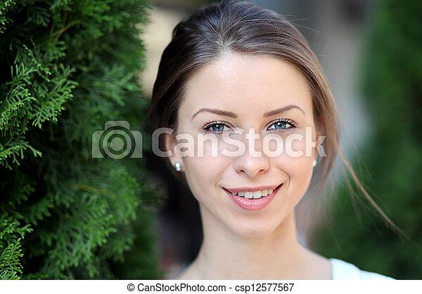 Beautiful young woman smiling - csp12577567