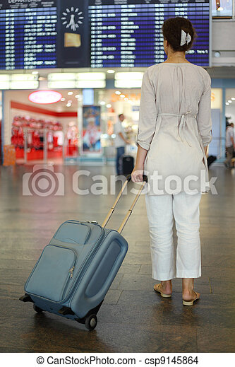 beautiful young woman standing in hall of airport with luggage and waiting airplane, focus on suitcase - csp9145864