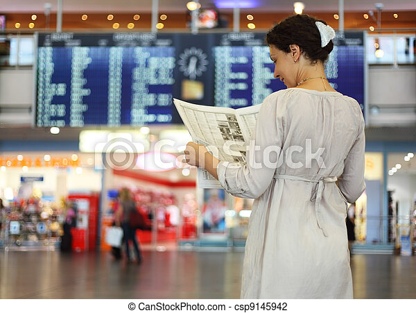 beautiful young woman standing in hall of airport and reading newspaper - csp9145942