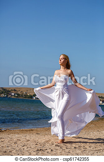 beautiful young woman standing in white dress by the sea on a Sunny day - csp61742355