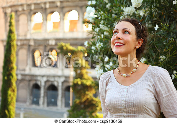 beautiful young woman stands near Colosseum and looks up, bush with white flowers - csp9136459