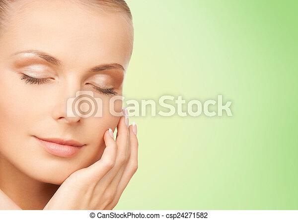 beautiful young woman touching her face - csp24271582