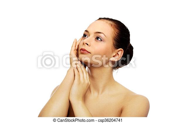 Beautiful young woman touching her face - csp36204741