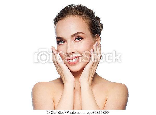 beautiful young woman touching her face - csp38360399