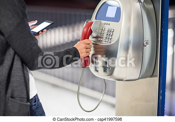 Beautiful young woman using a public phone in an airport - csp41997598