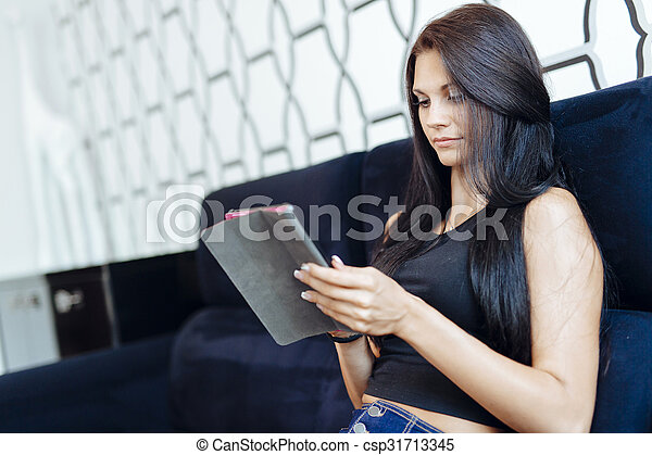 Beautiful young woman using a tablet - csp31713345
